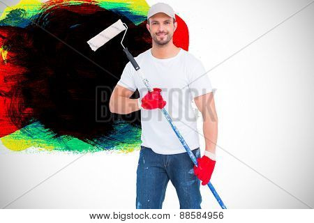 Handyman holding paint roller against red green black yellow and blue paint