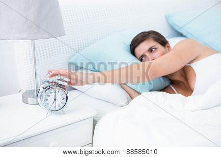 Pretty brunette extending hand to alarm clock at home in the bedroom