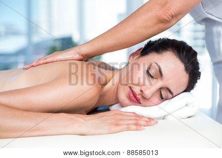Smiling brunette getting back massage in a healthy spa
