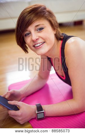 Fit woman looking at camera and using tablet pc on mat at home in the living room