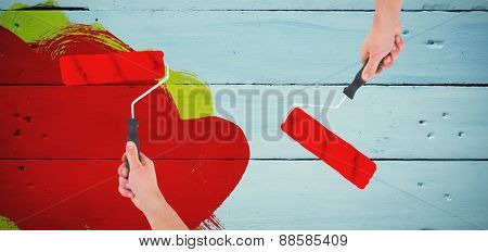 Handyman holding paint roller against painted blue wooden planks