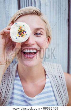 Pretty blonde woman grimacing with cupcake on wooden background