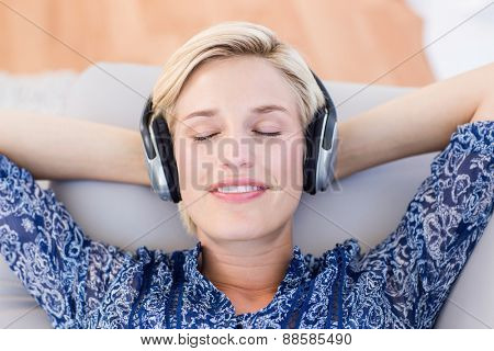 Pretty blonde woman listening music on the couch in the living room