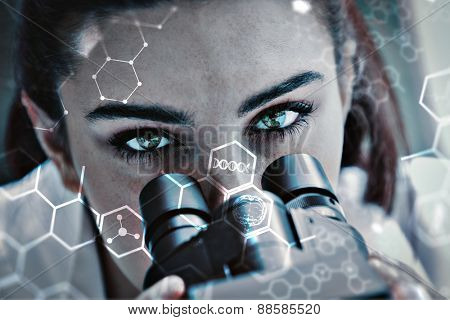 Close up of a scientist posing with a microscope against science and medical graphic