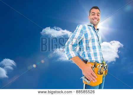 Portrait of smiling handyman wearing tool belt against sky