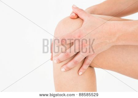 Natural woman touching her painful knee on white background