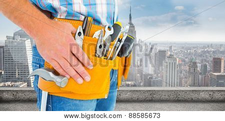 Midsection of handyman wearing tool belt against large city