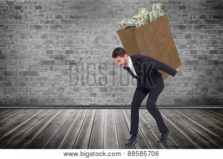 Businessman carrying something heavy with his back and hands against grey room