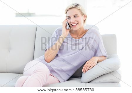 Pretty blonde woman calling on the phone in the room