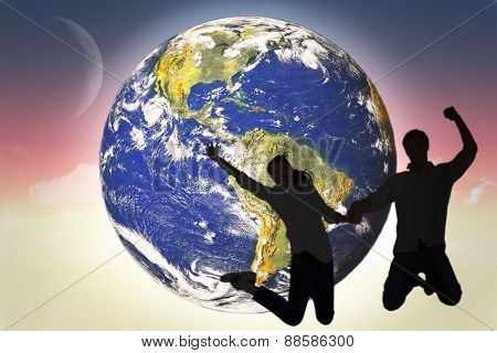 Couple jumping and holding hands against magical sky
