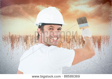 Portrait of happy man using paintbrush against sun shining over city