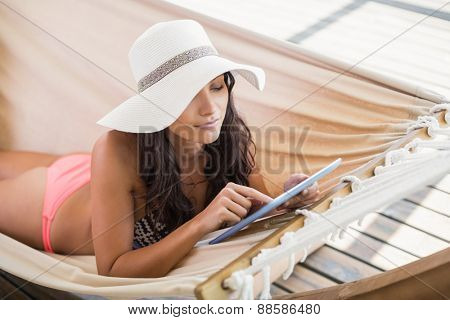 Pretty brunette relaxing on a hammock and using tablet pc in patio