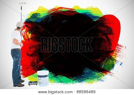 Man using paint roller on white background against red green black yellow and blue paint