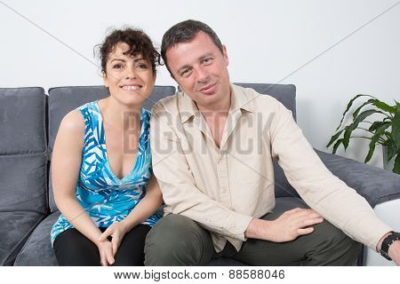 Couple Being Playful On A Grey Sofa At Home.