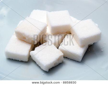 Many sugar cube on dish close up