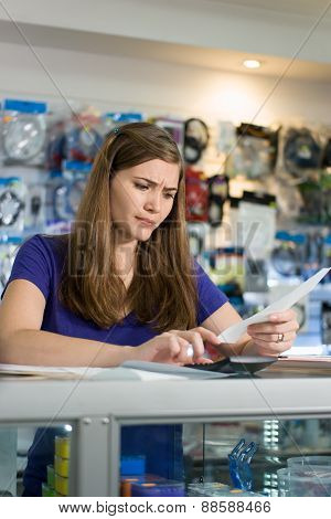 Worried Woman Checking Bills And Invoices With Calculator
