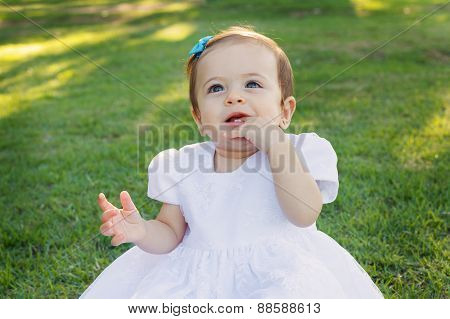 Cute happy smiling little baby girl scratching first teeth