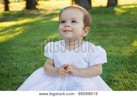 Cute Happy Little Smiling Baby Girl In White Dress