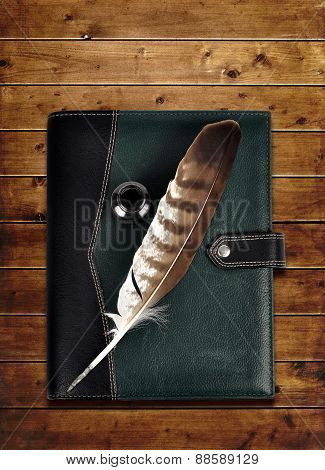 Leather notebook and feather with ink bottle.