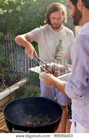 man helping at the outdoor garden barbeque with a plate while man serves healthy chicken meat