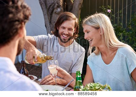 young couple enjoying white wine outdoors at garden party
