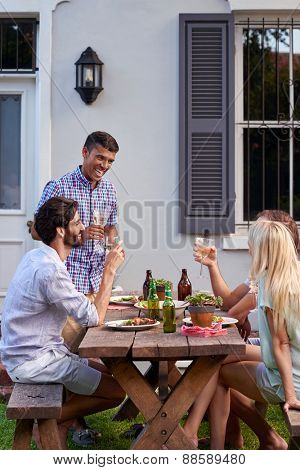 Man toasting speech at friends outdoor garden party with wine drinks