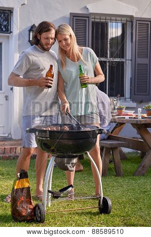 Women helping boyfriend husband at outdoor garden barbecue with tongs and beer