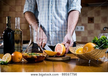 Man cuts fresh grapefruits