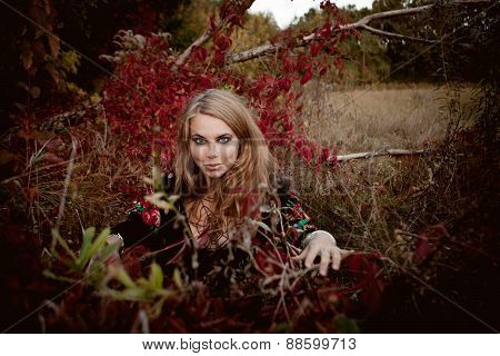 Beautiful Young Girl In Black Dress Standing Among Colorful Leaves