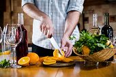 foto of sangria  - Man cuts oranges for making sangria for home party - JPG