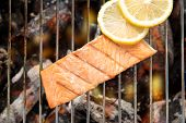 picture of flame-grilled  - Top view grilled salmon with lemon on the flaming grill - JPG