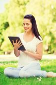 Постер, плакат: lifestyle summer vacation technology and people concept smiling young girl with tablet pc sitti