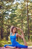 pic of sportswear  - Flexible girl in sportswear doing yoga exercise for stretching in park - JPG