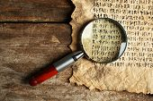 image of hieroglyph  - Grunge paper with hieroglyphics with magnifier on wooden background - JPG