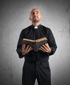 stock photo of priest  - Priest praying and reading the sacred scripture - JPG