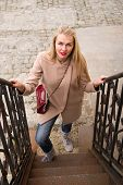 stock photo of exaltation  - Young woman in coat smiles and walks up the stairs - JPG