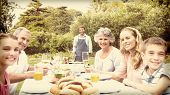 stock photo of extended family  - Happy extended family waiting for barbecue being cooked by father smiling at camera - JPG