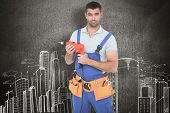 pic of overalls  - Confident male carpenter in overall holding drill machine against hand drawn city plan - JPG