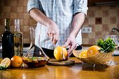 pic of sangria  - Man cuts fresh grapefruits for making sangria for home party - JPG