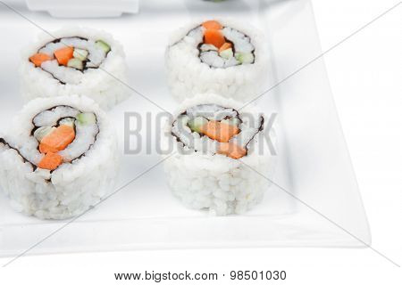 Japanese Cuisine - California Maki Roll made of Smoked Salmon, Cream Cheese and Deep Fried Vegetables inside. With wasabi . isolated over white background on square plate