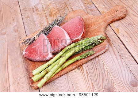 meat food : raw beef fillet on cutting board with asparagus and thyme bundle , with color peppercorn mix and red paprika powder mixed with dry spices ready to cooking