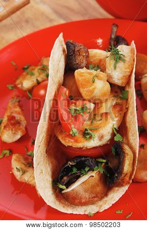 big mexican taco with tomatoes and mushroom, served with soup, fresh vegetables , on red crockery plates over wooden table with cutlery and napkin