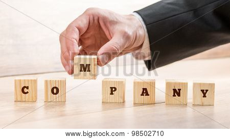 Closeup Of Male Hand Putting Together Word Company On Seven Wooden Cubes. Conceptual Of Building A C
