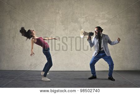 Man screaming into a megaphone towards a woman