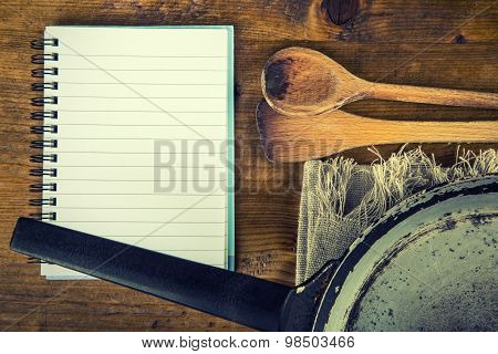 Wooden kitchen utensils on the table. Recipe book wooden spoon old pan in a retro style