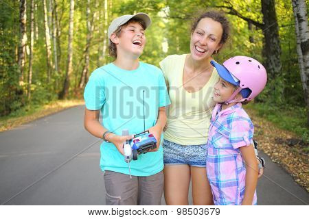 Boy with the car and remote control laughing with mother and younger sister in the green park