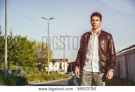 Young man in black leather jacket walking along city street