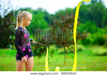 Young gymnast warms up with a gymnastic tape or feed