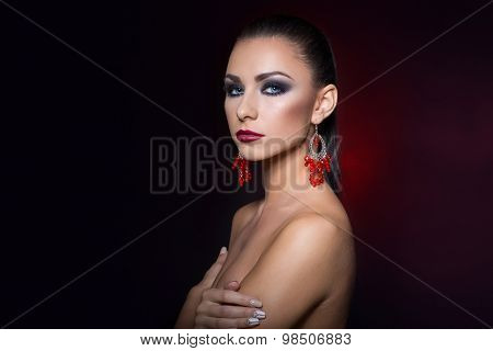 expensive jewelry wreath earrings and ring on a beautiful sexy nude elegant brunette girl with bared