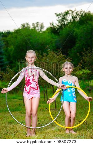 fitness, sport, people and healthcare concept - little sporty girls exercising with hula hoop over p